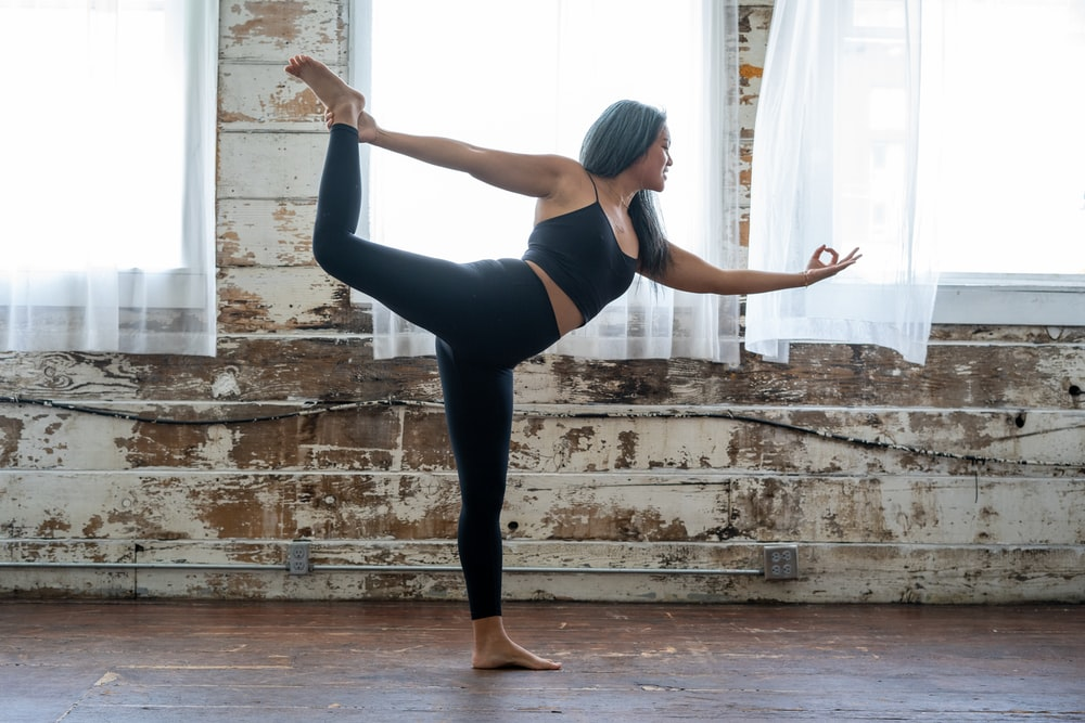 woman in black tank top and leggings doing yoga