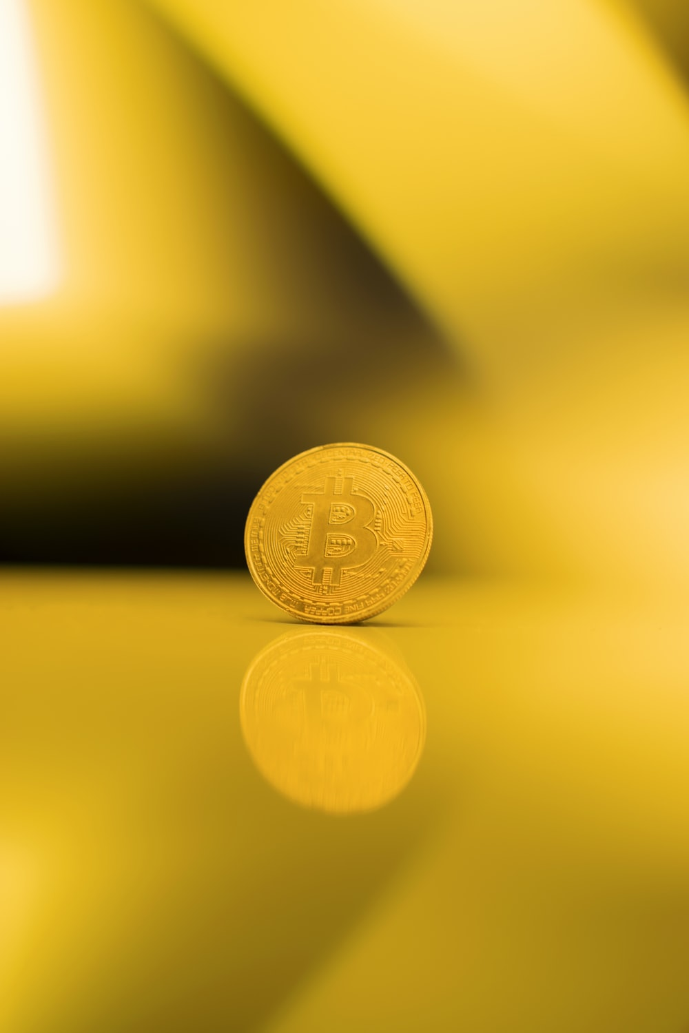 gold round coin on yellow surface