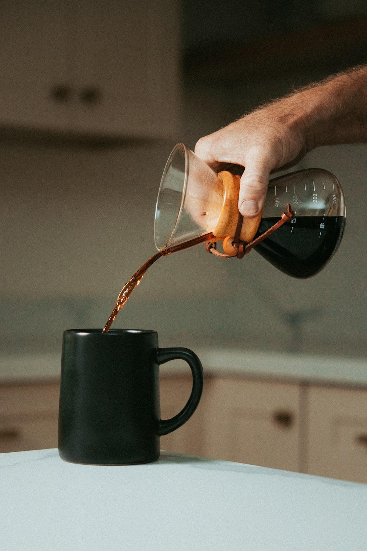 person pouring tea on black ceramic mug