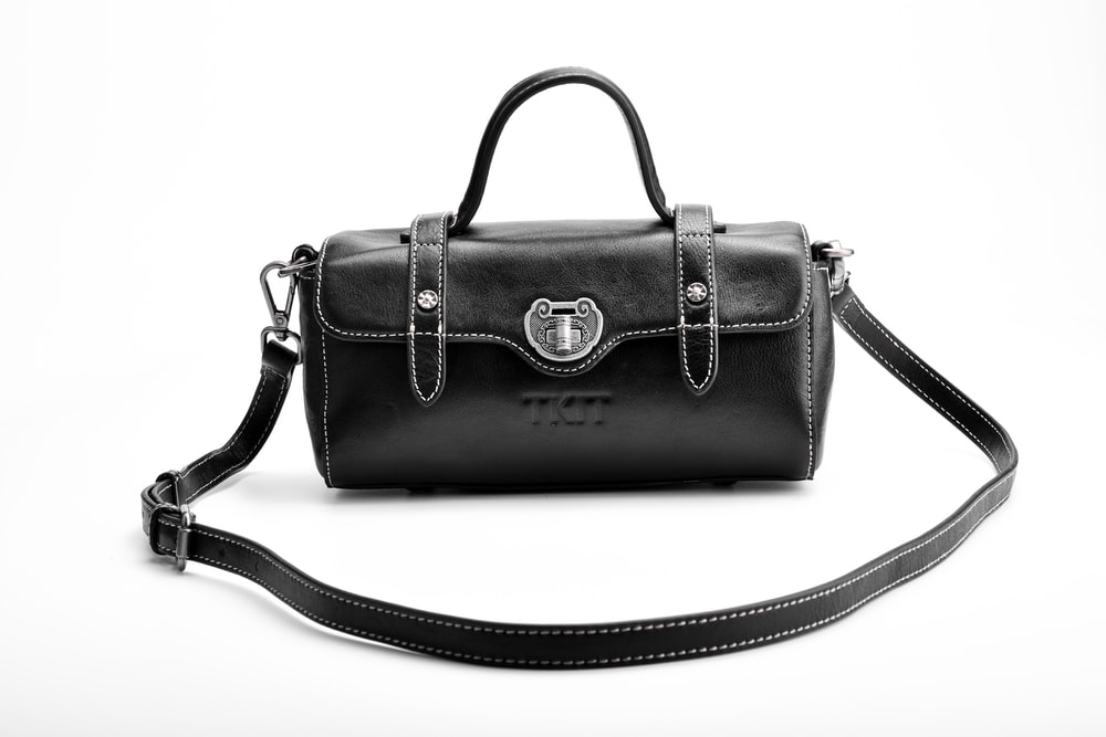 black leather handbag on white surface
