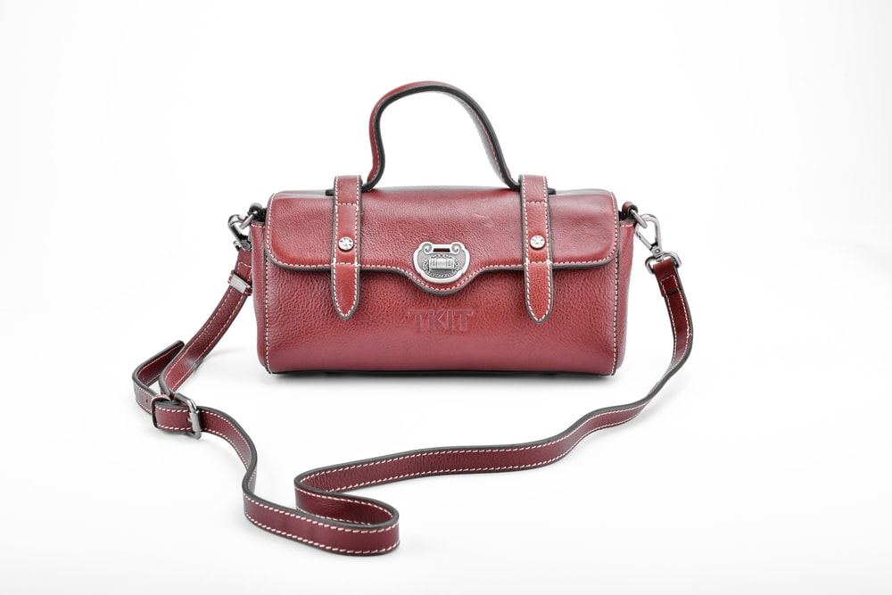 brown leather sling bag on white surface