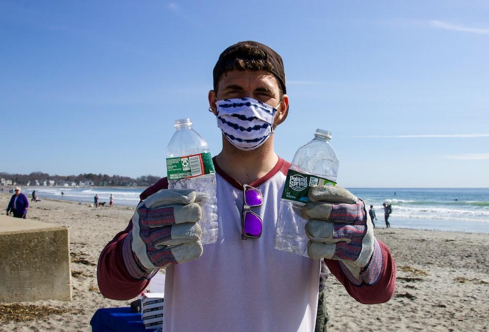 man in white shirt holding bottled water