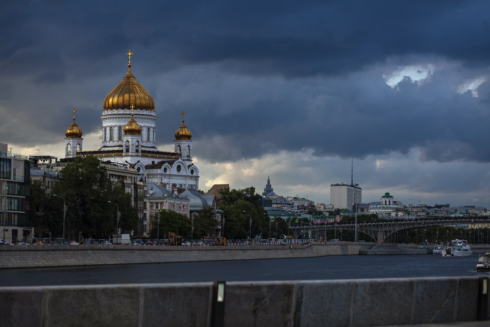 white and gold dome building under cloudy sky during daytime