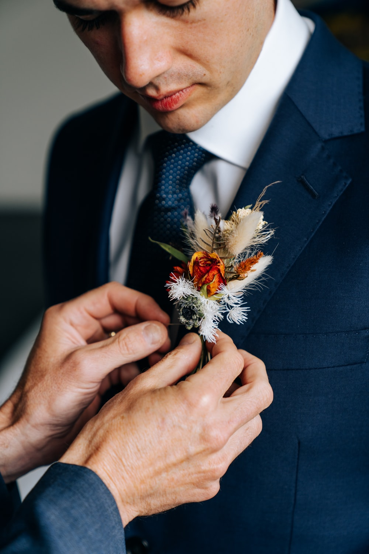 man in black suit holding white flower