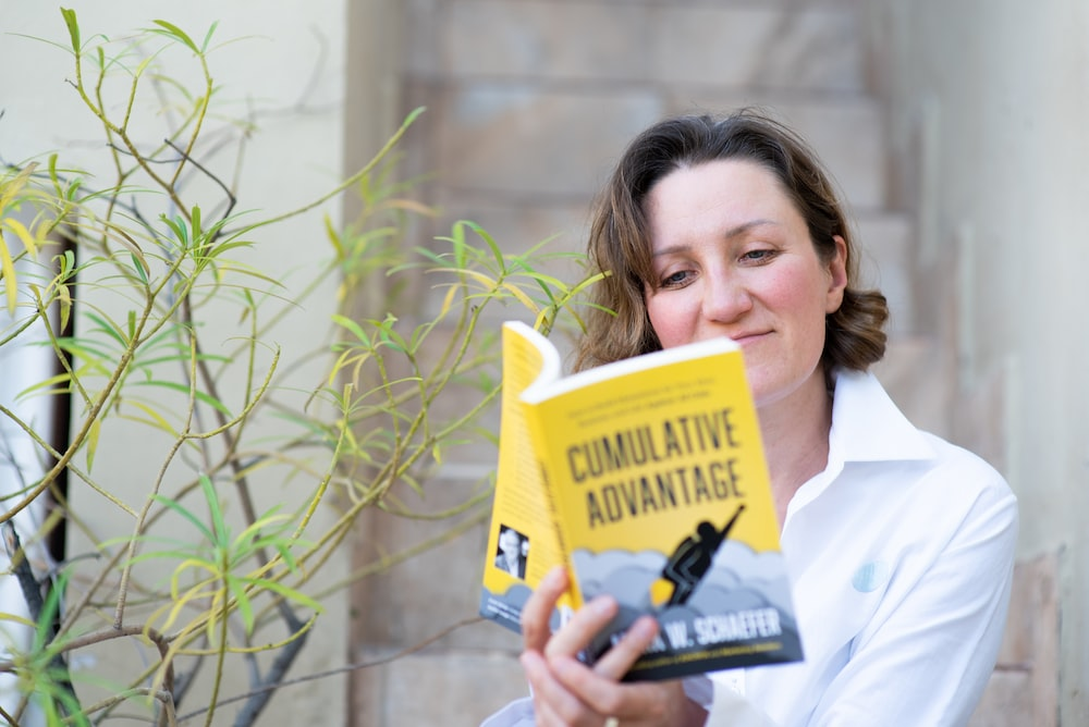 woman in white dress shirt holding yellow book