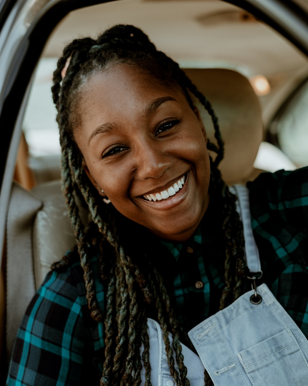 smiling woman in blue and black plaid shirt