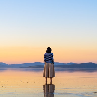 woman in black and white dress standing on beach during sunset