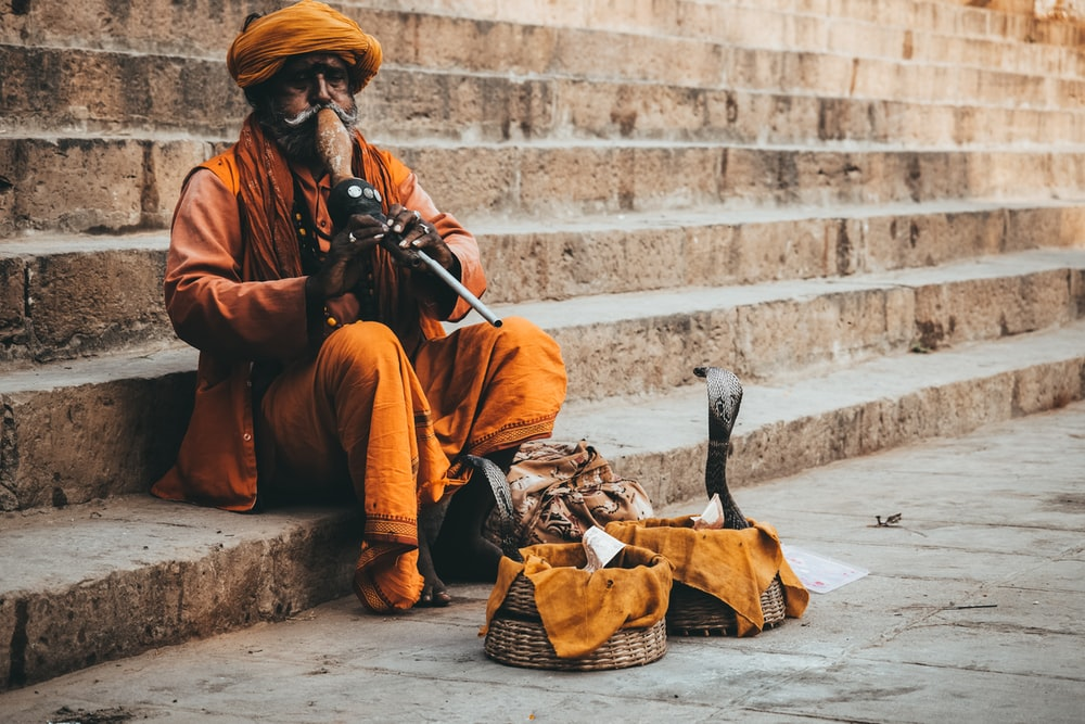 man in orange thobe sitting on concrete stairs
