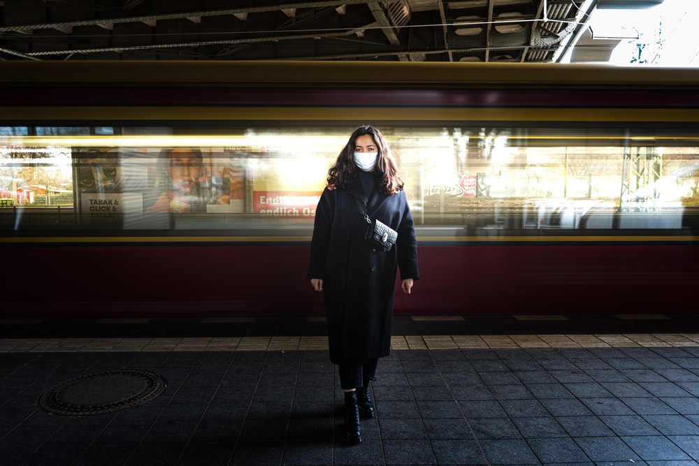 woman in black long sleeve dress standing on train station