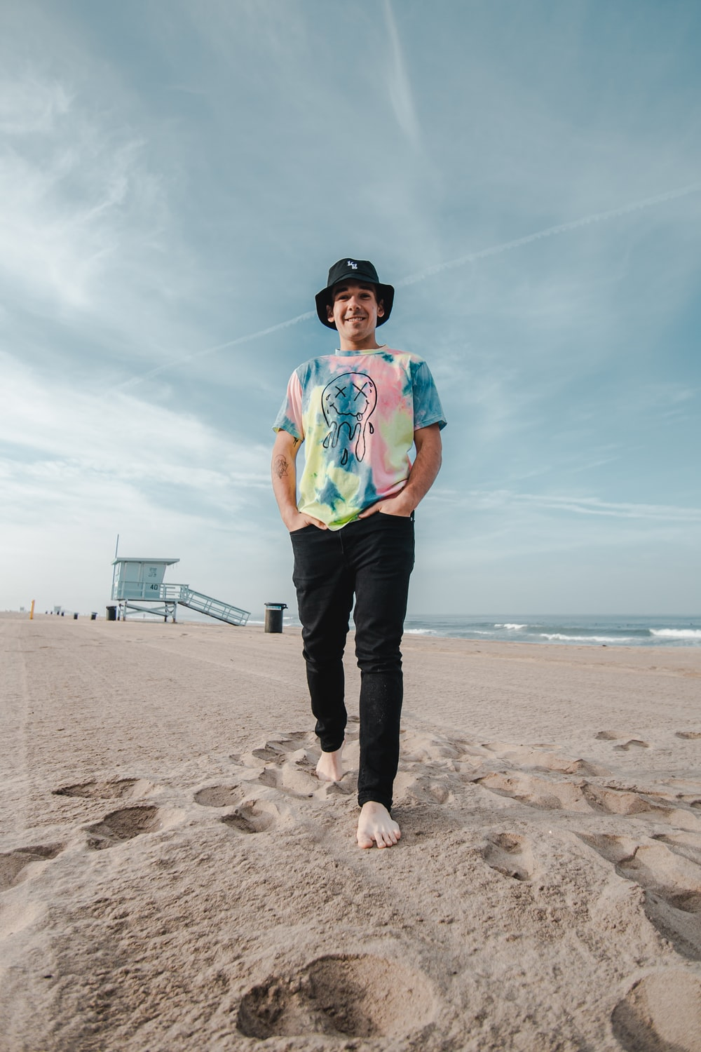 man in blue shirt and black pants standing on beach shore during daytime
