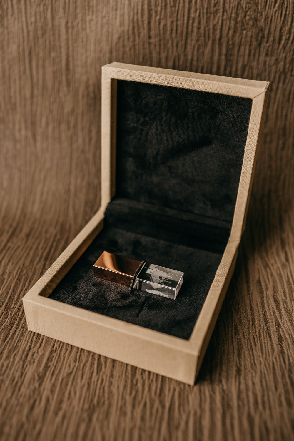 silver ring in box on brown wooden table