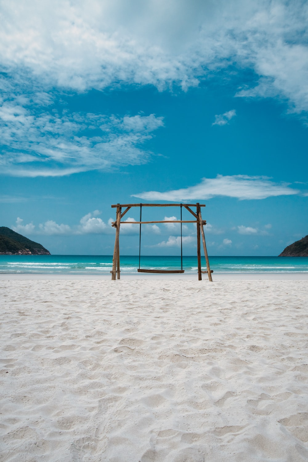 brown wooden swing on white sand beach during daytime
