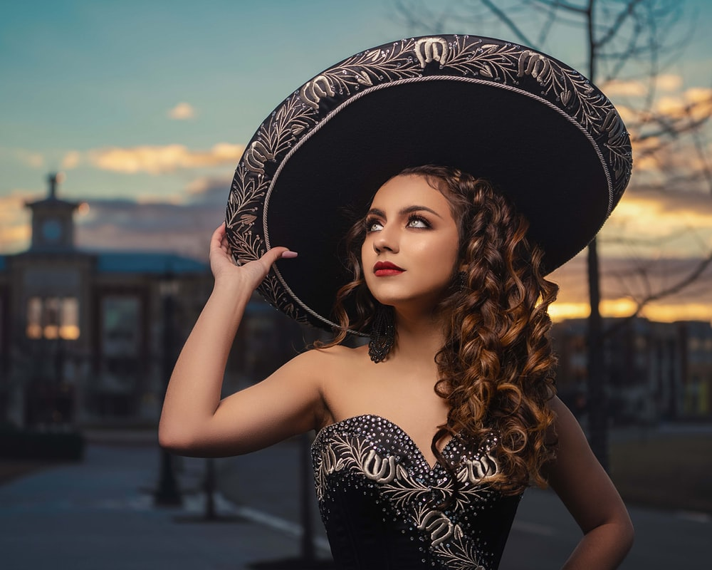 woman in black and white floral hat and black tube dress