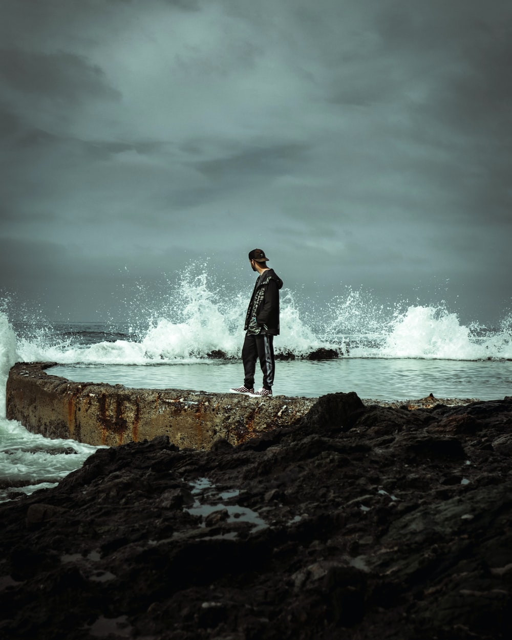 man in black jacket standing on rock near ocean waves