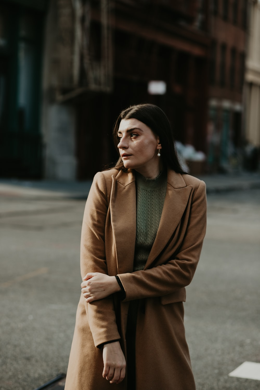 woman in brown coat standing on sidewalk during daytime