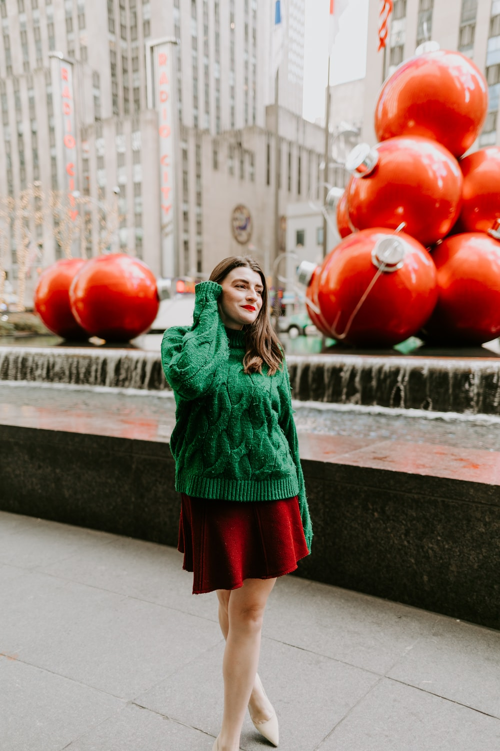 woman in green long sleeve dress holding red balloons
