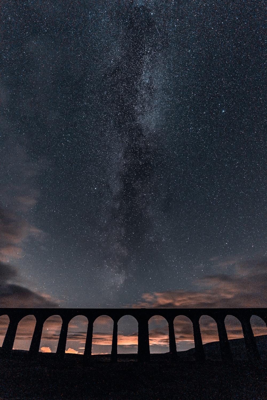 brown concrete bridge under starry night