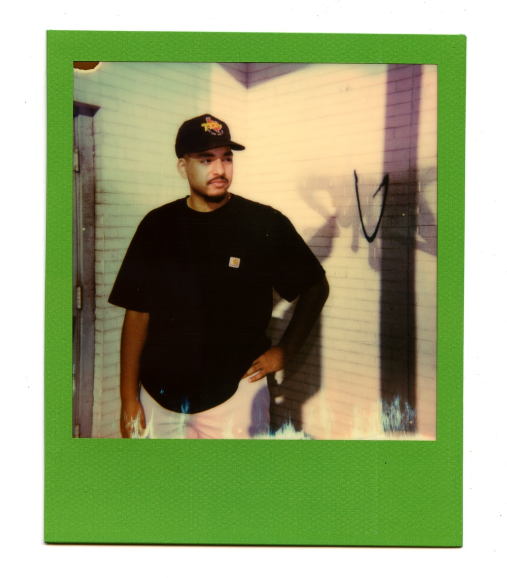 man in black crew neck t-shirt and black cap standing near green wall