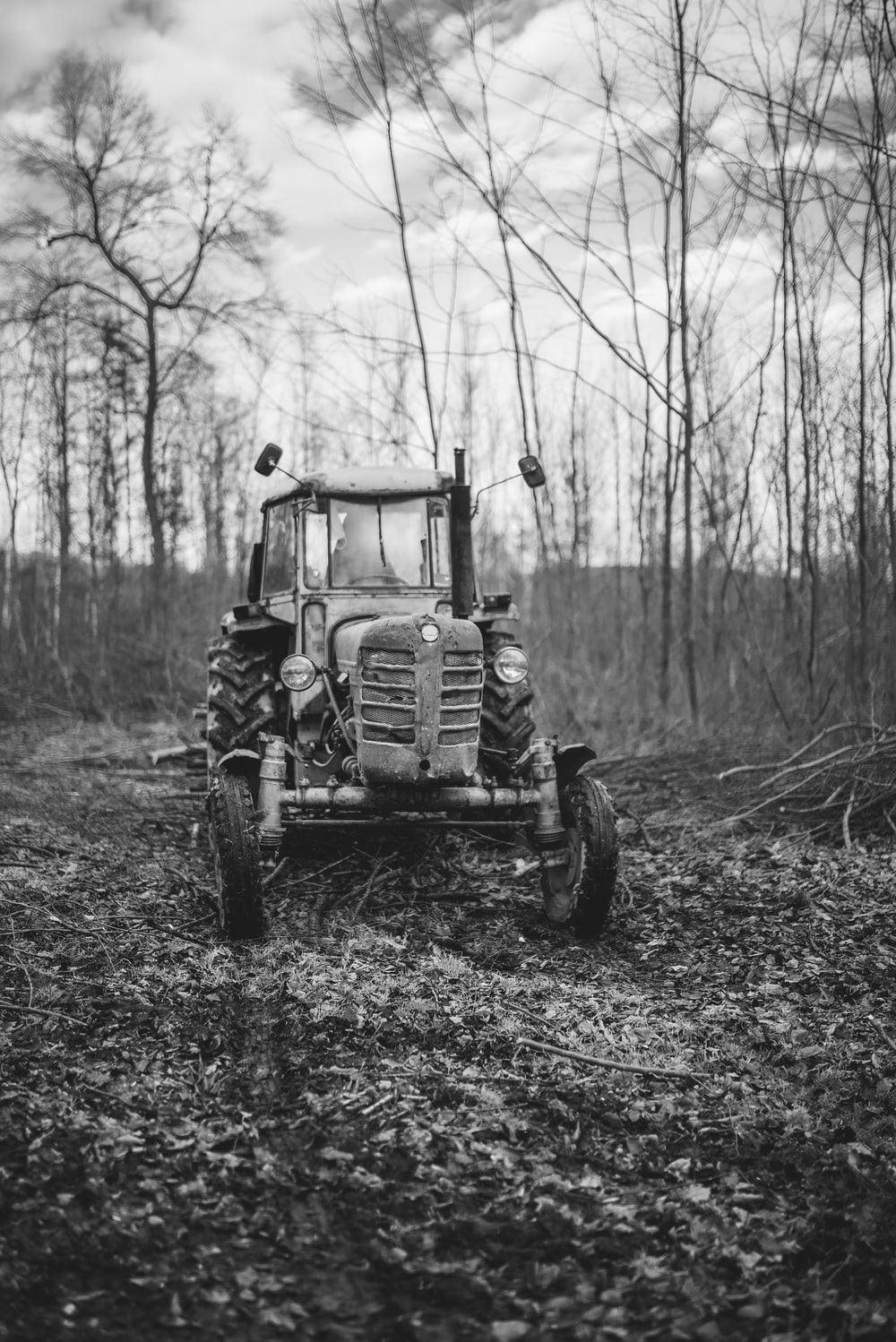 grayscale photo of tractor in forest