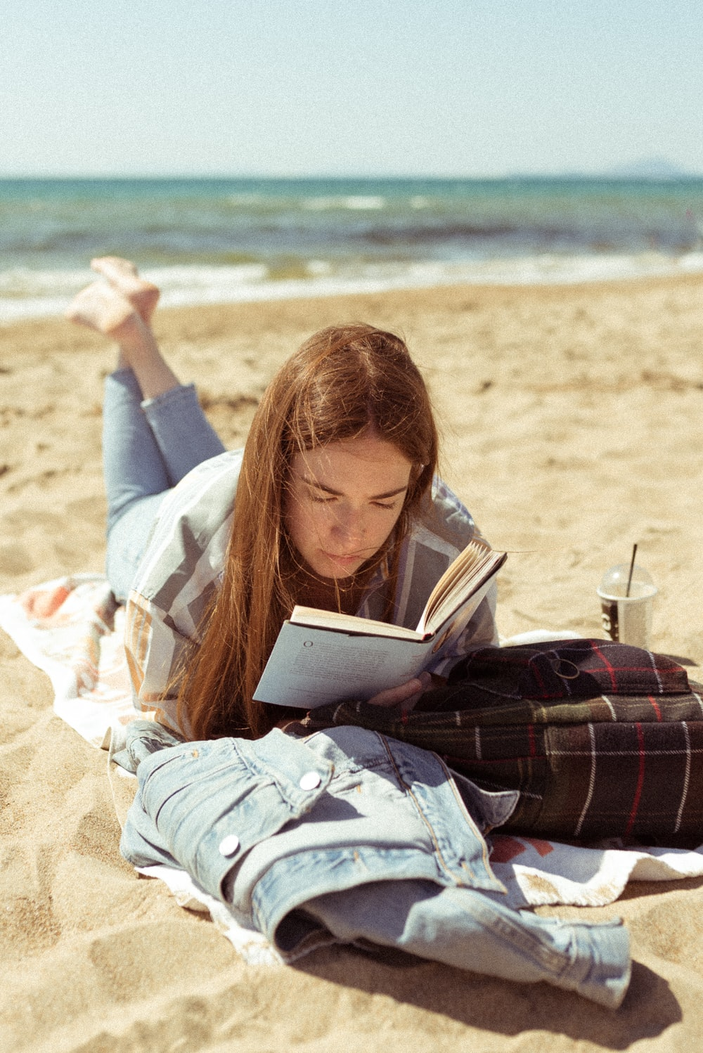 woman in white long sleeve shirt reading book on beach during daytime