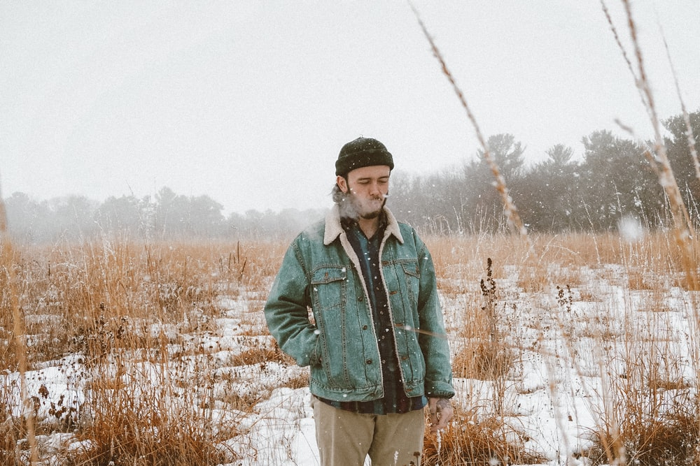 man in green jacket standing on brown grass field during daytime