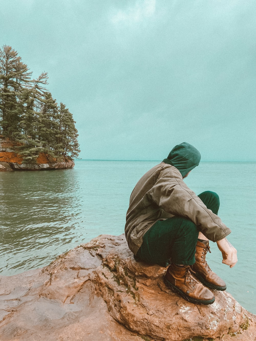 man in green hoodie and brown pants sitting on brown rock near body of water during