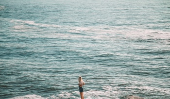 woman in white shirt and black shorts standing on sea shore during daytime