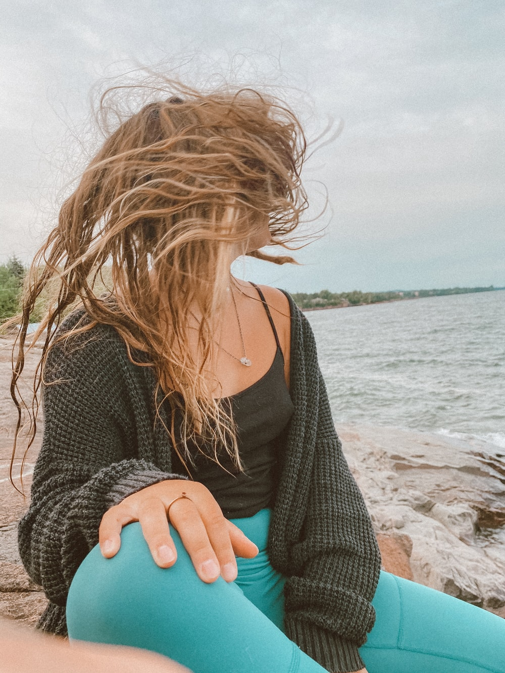 woman in black knit sweater sitting on beach shore during daytime