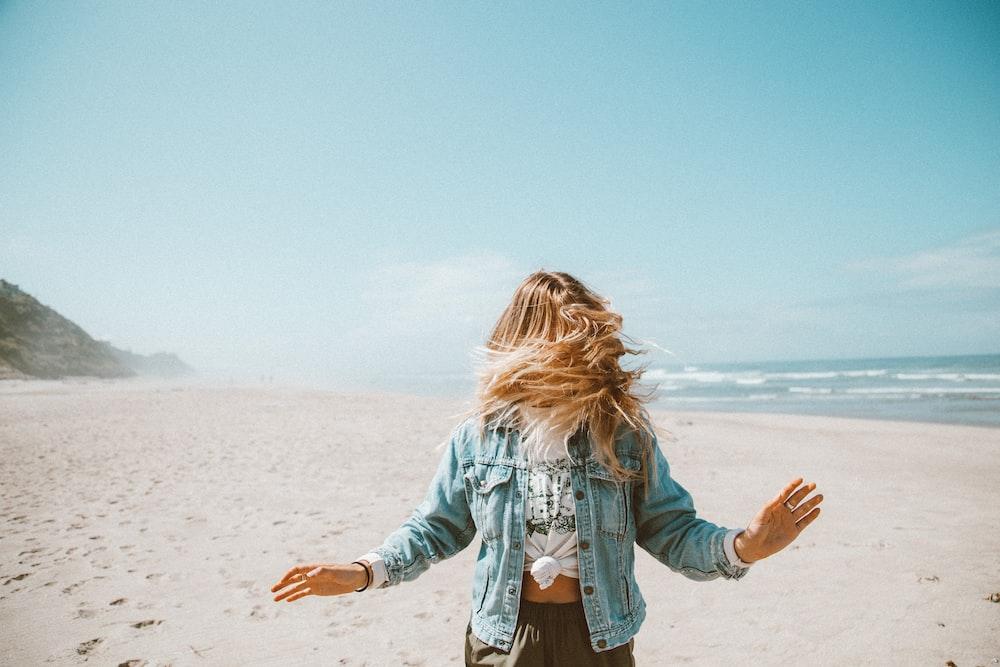 girl in blue denim jacket standing on beach during daytime