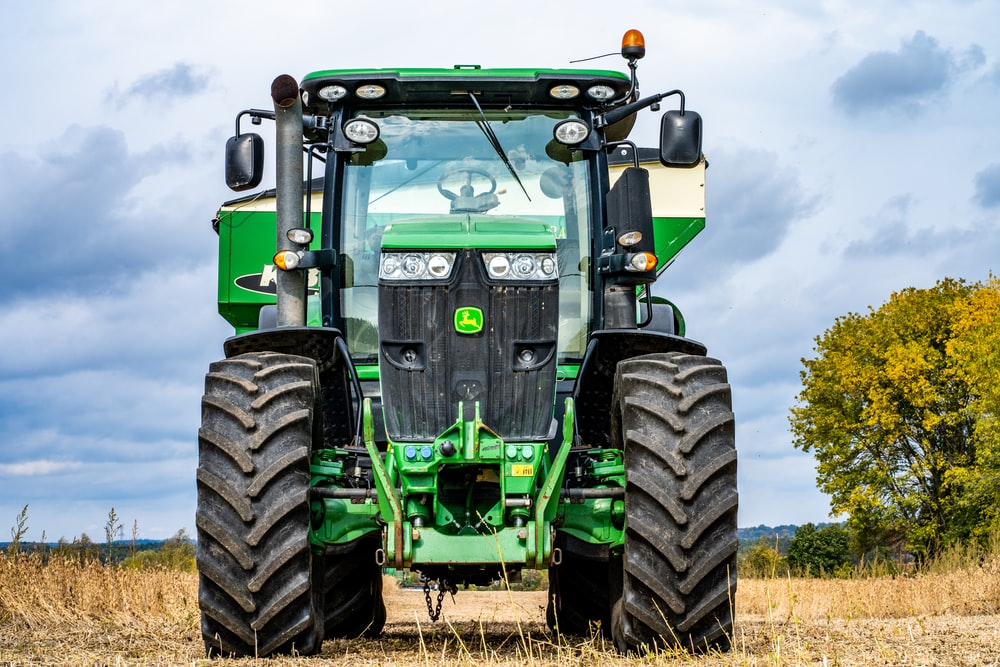 green and black tractor on brown grass field during daytime