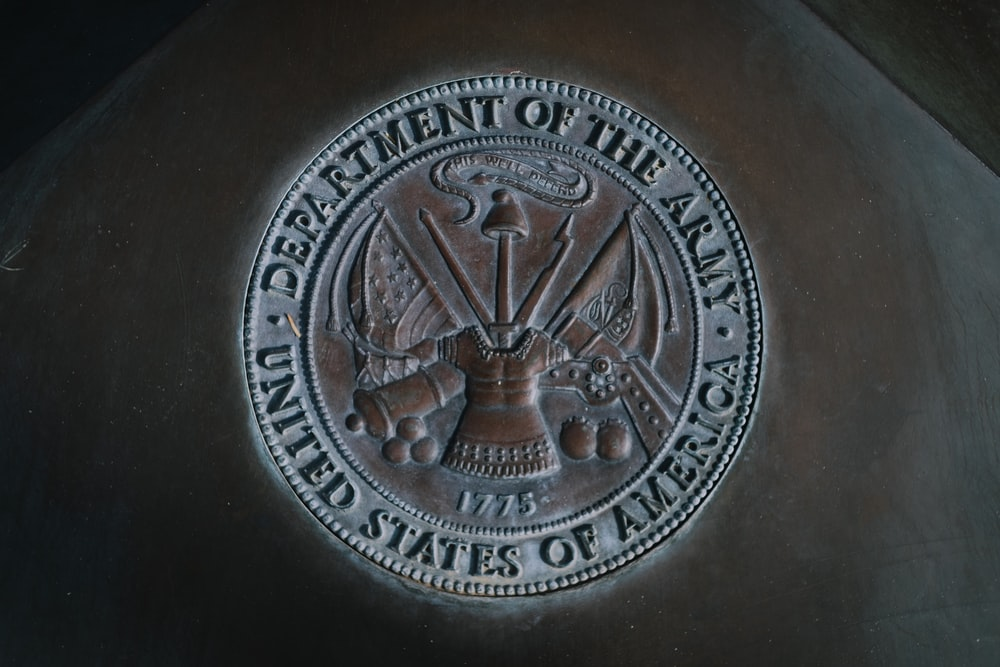 silver round coin on black textile