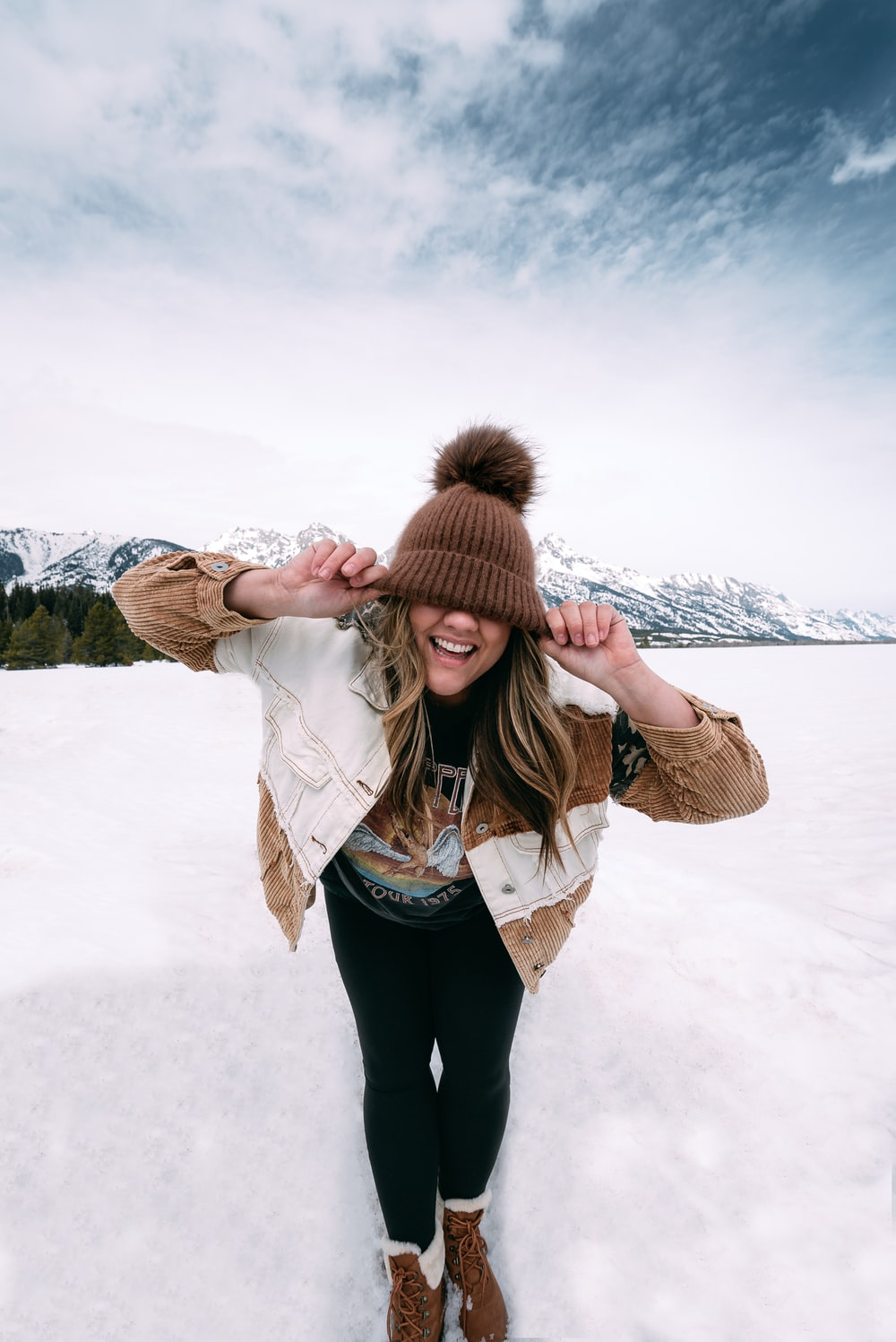 woman in brown parka jacket standing on snow covered ground during daytime
