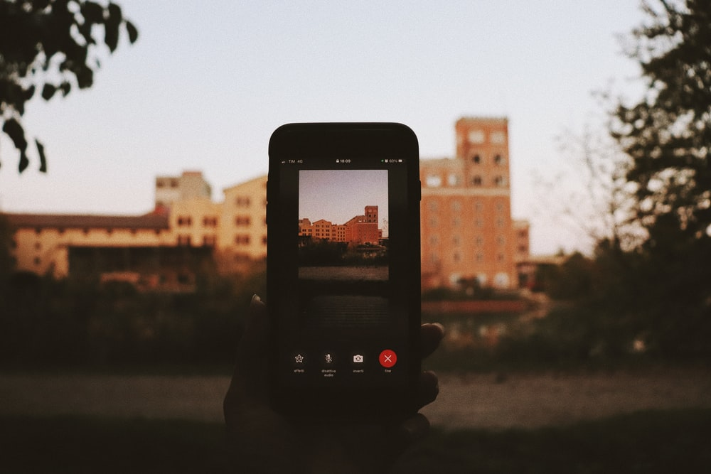person taking photo of city buildings during daytime