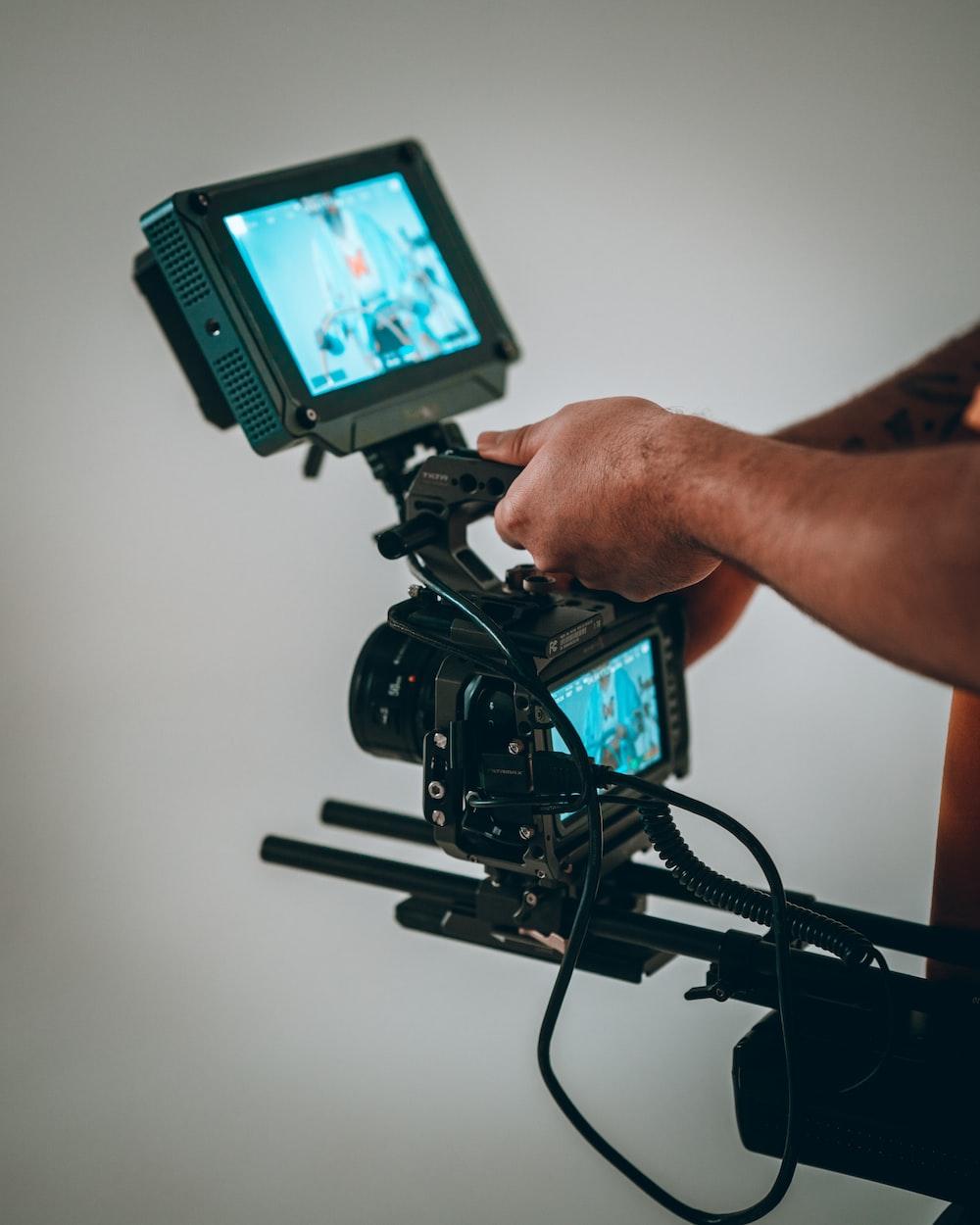 person holding black video camera