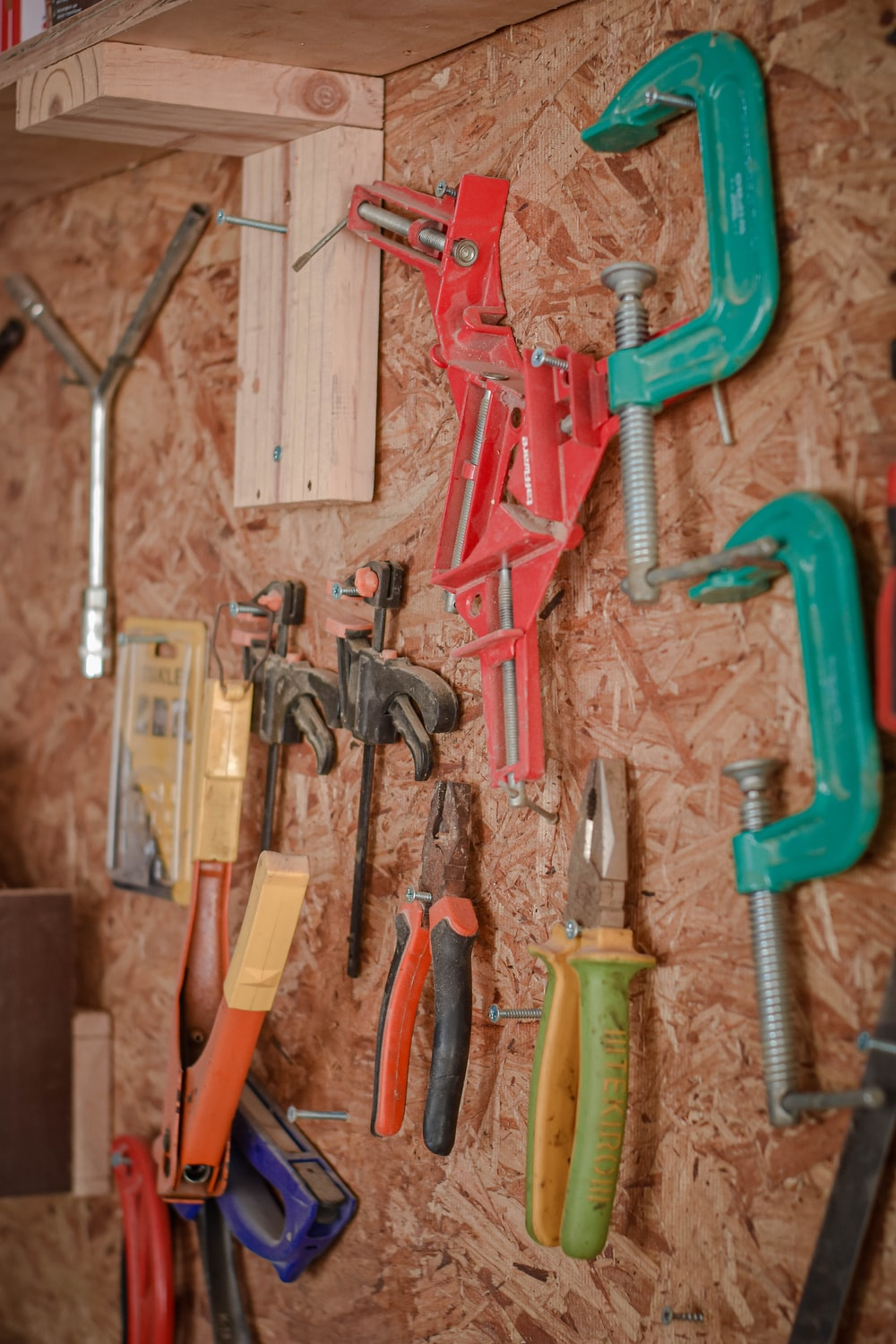 assorted hand tools on brown wooden wall
