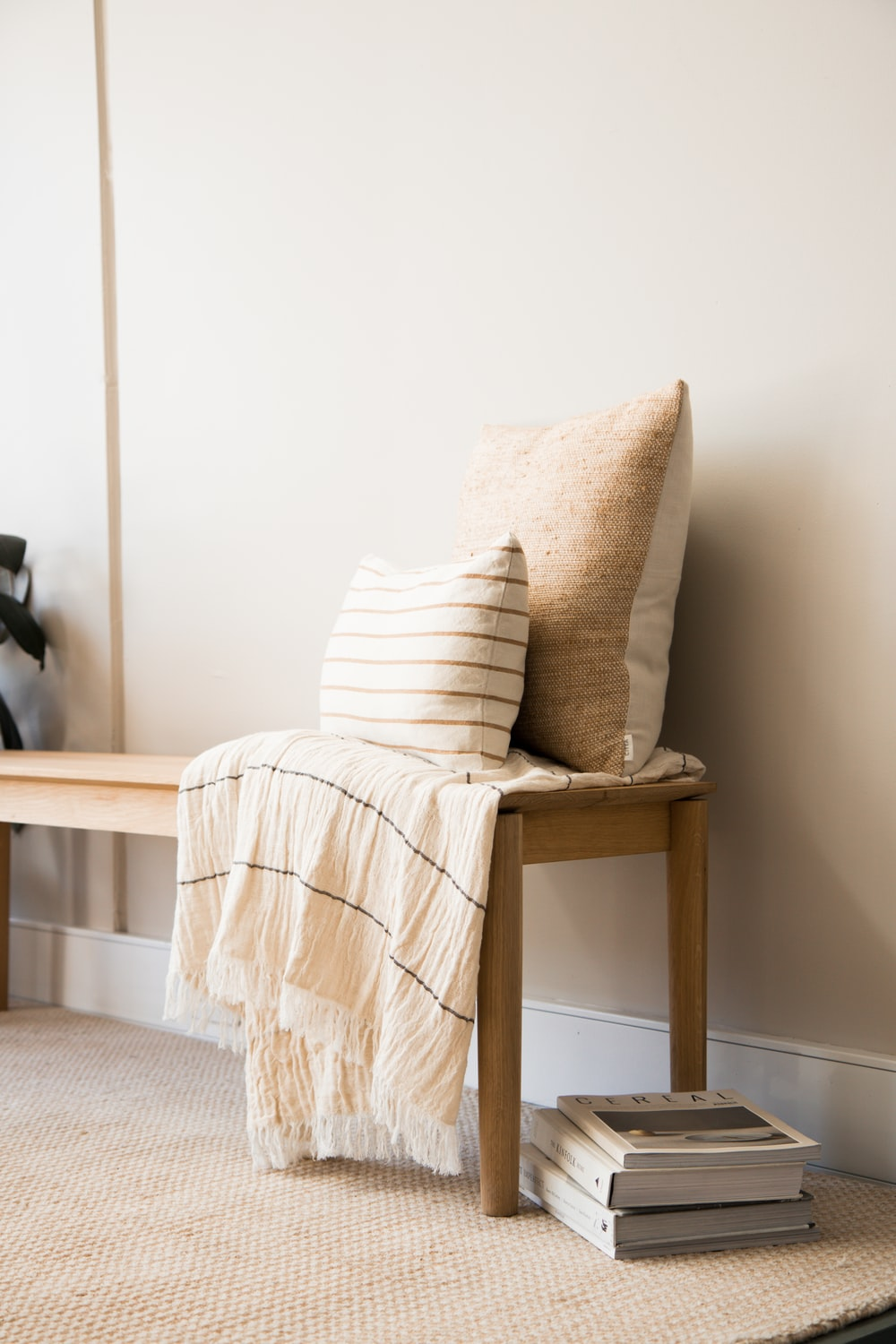 white and brown throw pillow on brown wooden chair