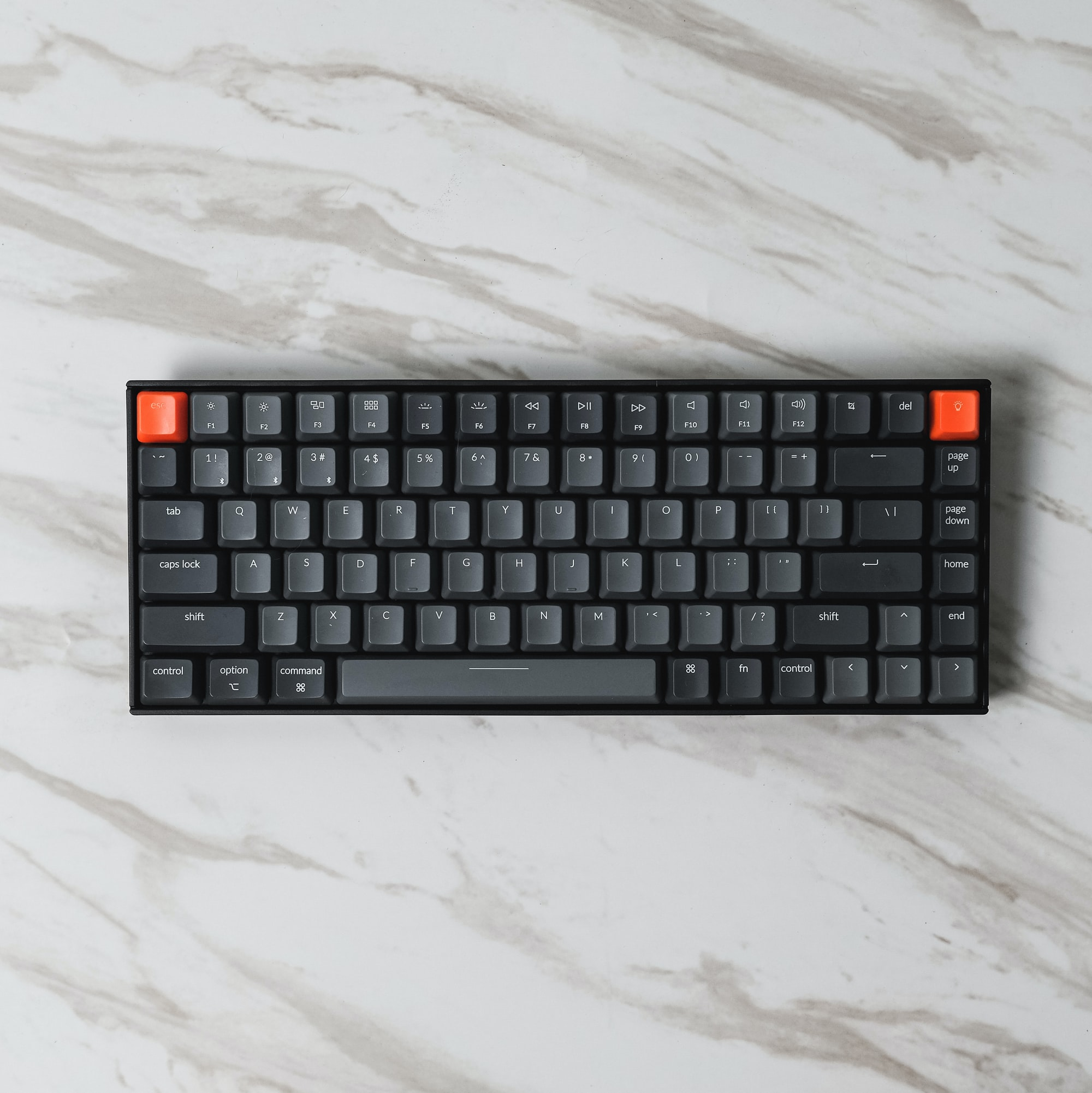 A black mechanical keyboard sitting on a marble surface