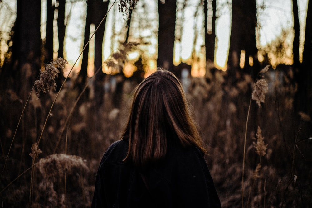 woman in black coat standing near trees during daytime