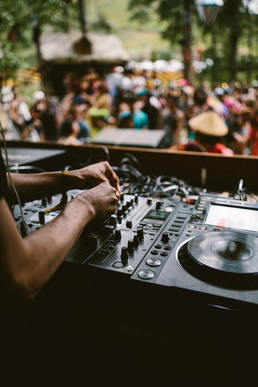 person playing dj mixer in tilt shift lens