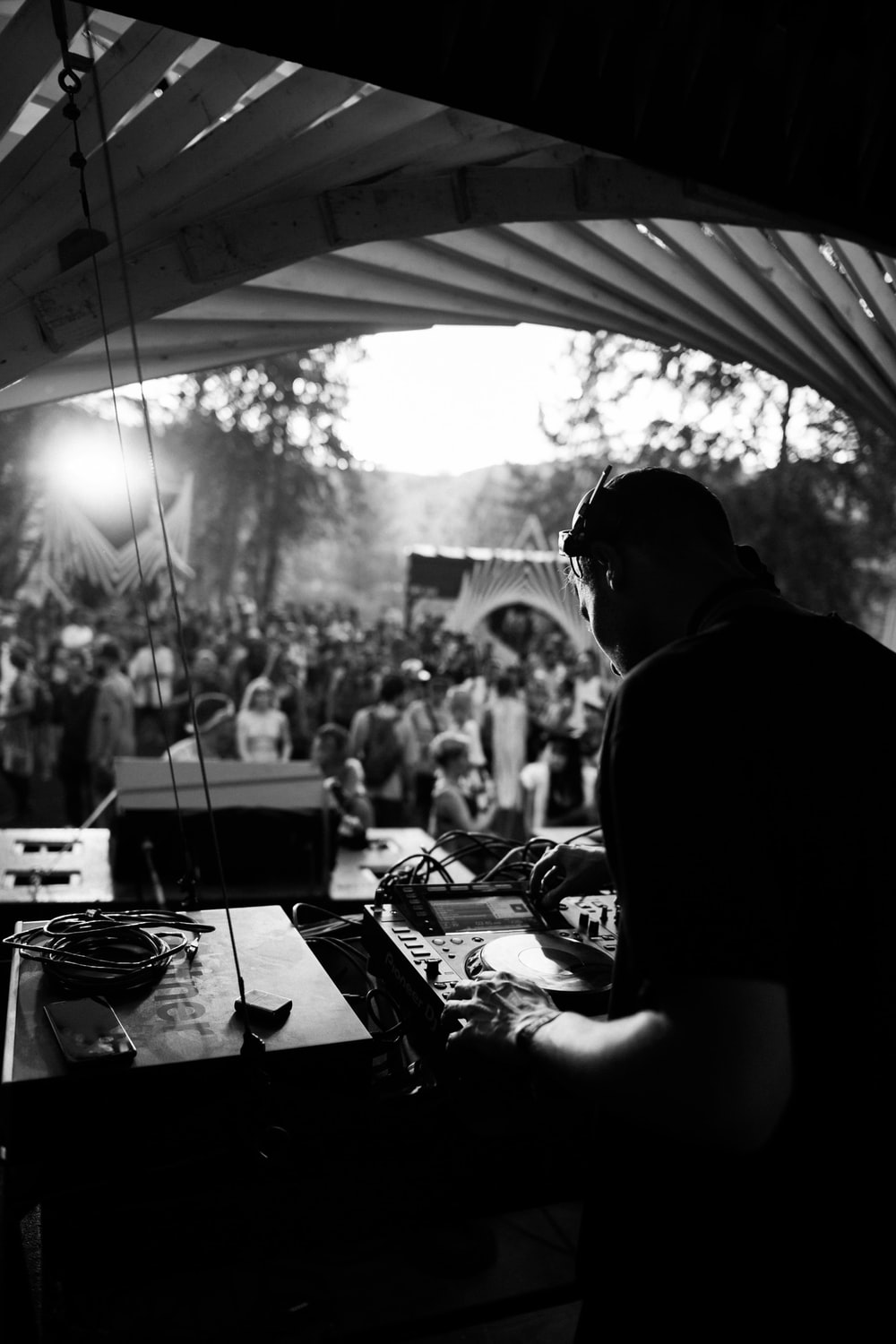 grayscale photo of man in black shirt playing dj controller