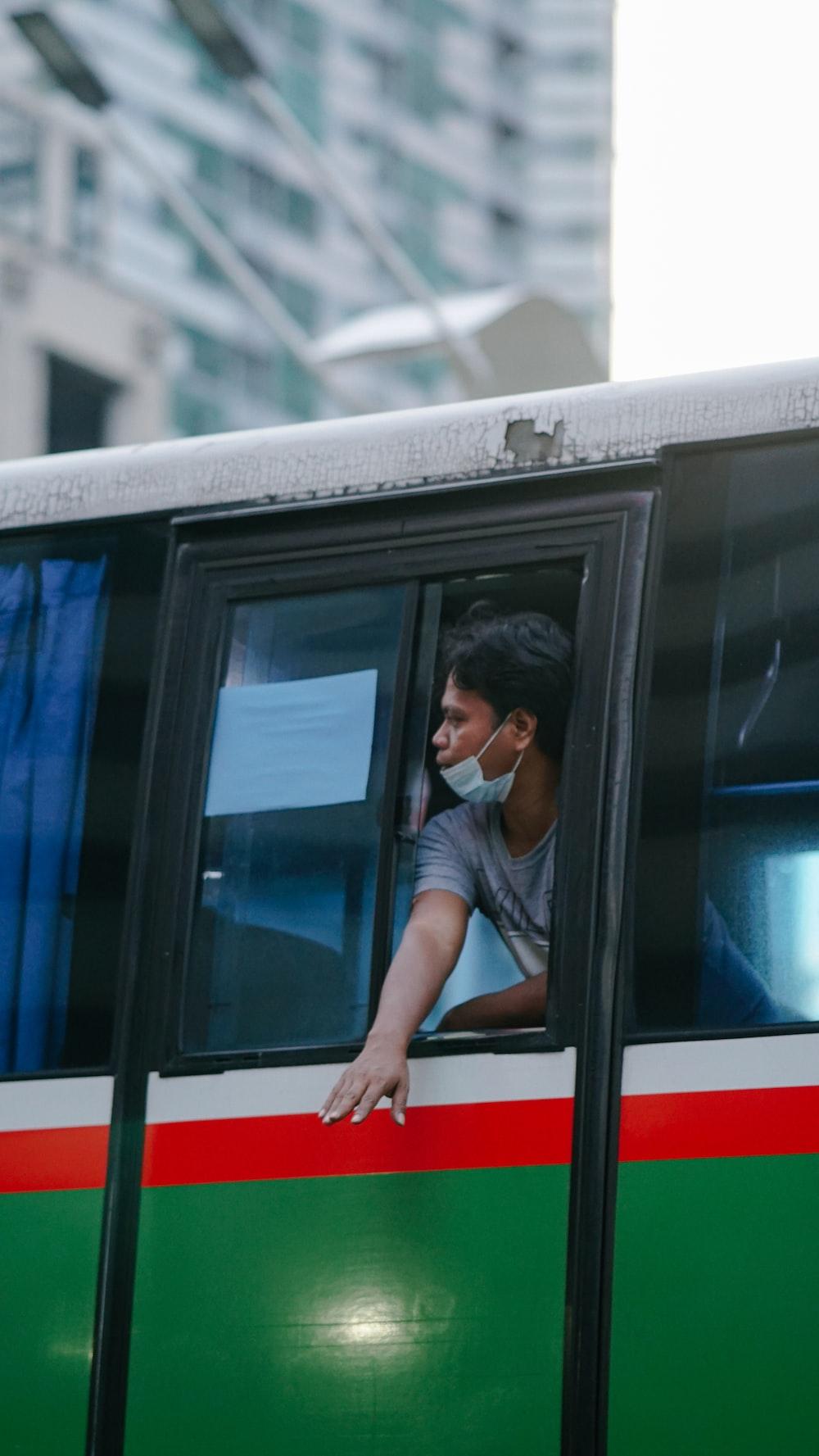 man in black t-shirt sitting on train window