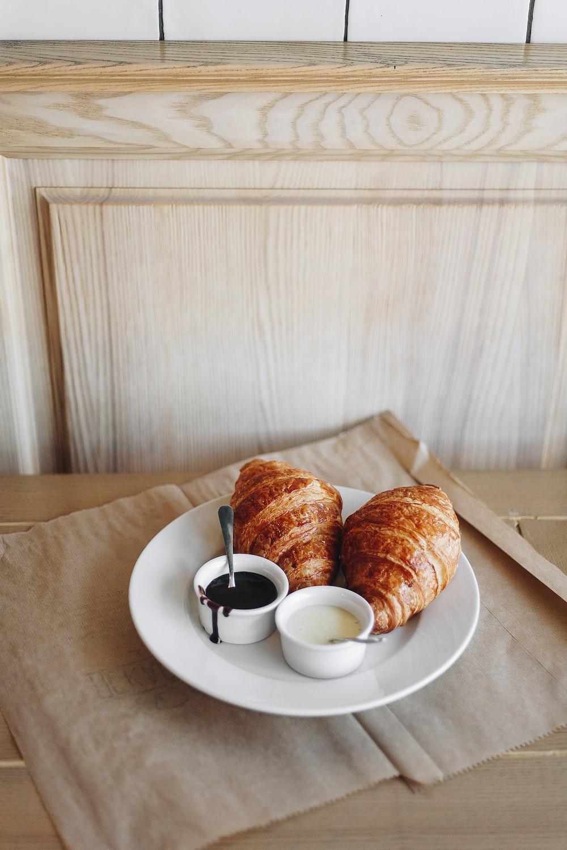 bread on white ceramic plate beside white ceramic teacup on saucer