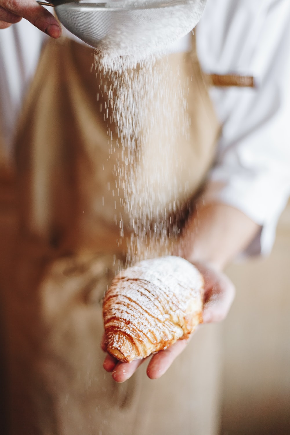person in white shirt holding brown bread