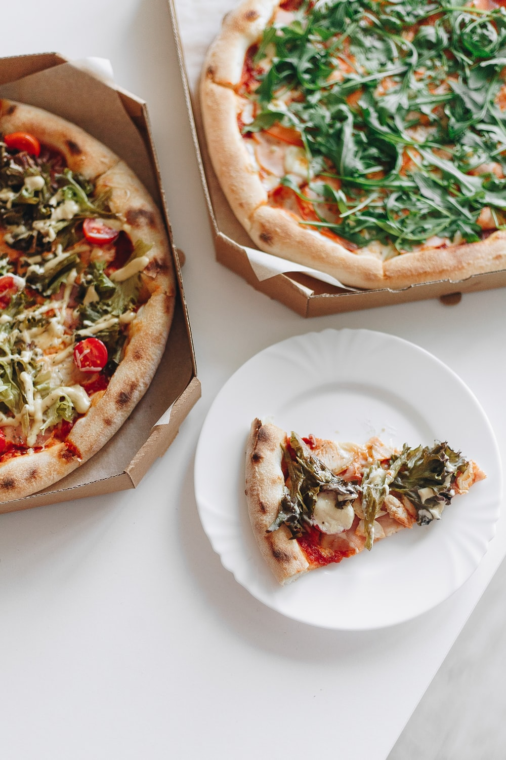 pizza with green leaf on white ceramic plate