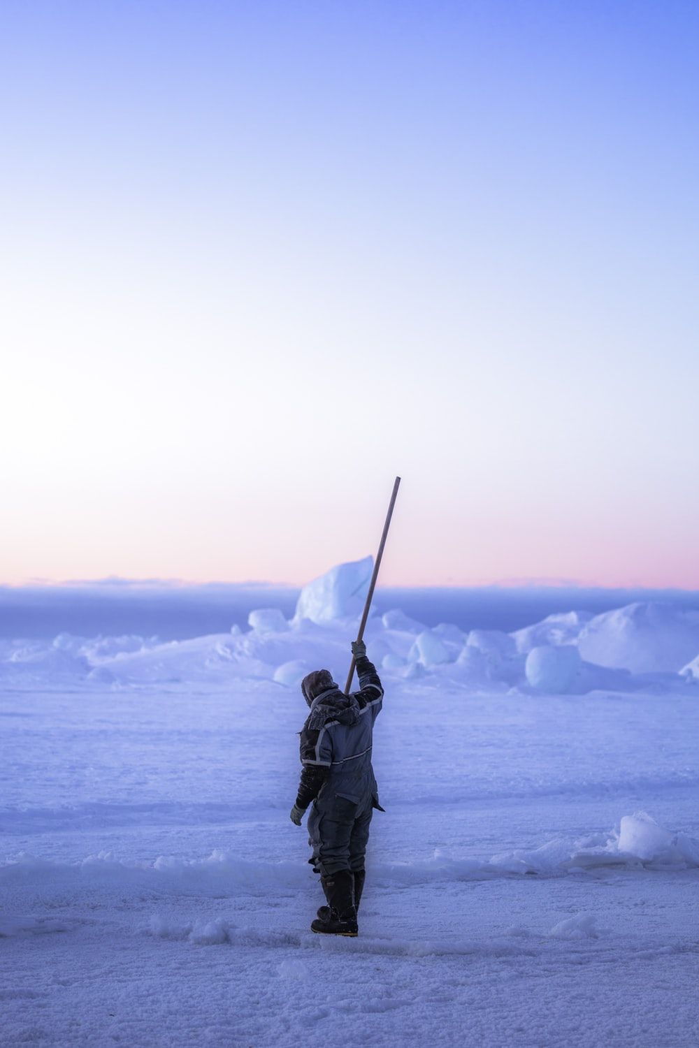 person in black winter jacket holding black stick on snow covered ground during daytime