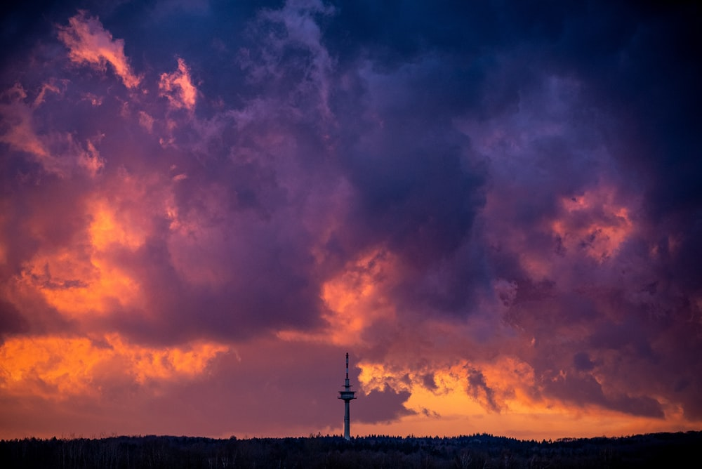 silhouette of windmill under cloudy sky during sunset