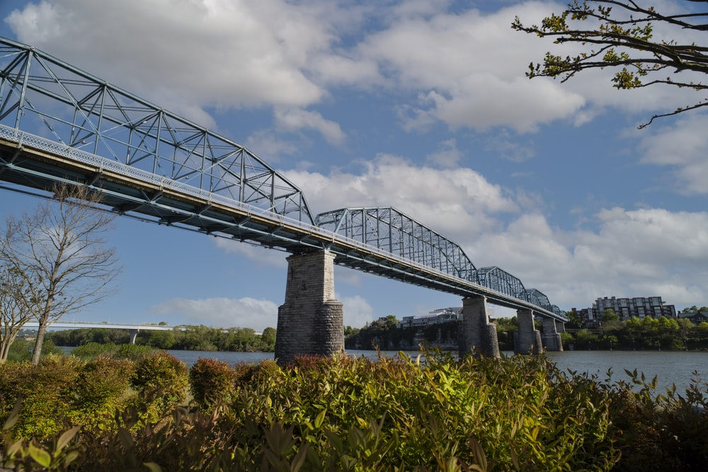 gray metal bridge under cloudy sky during daytime