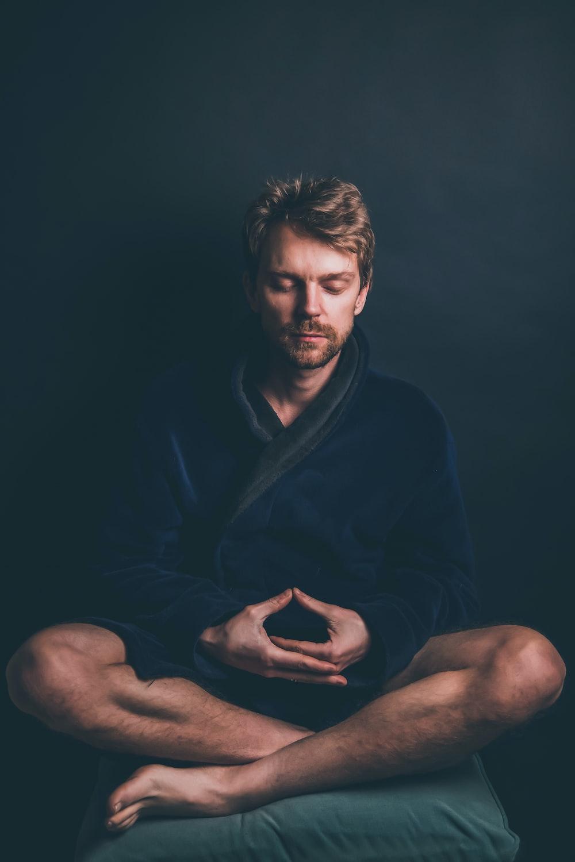 man in black hoodie sitting on black background