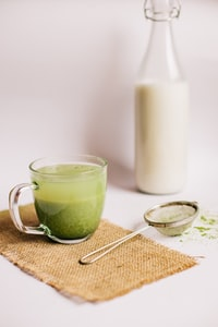 green liquid in clear glass mug beside white pillar candle