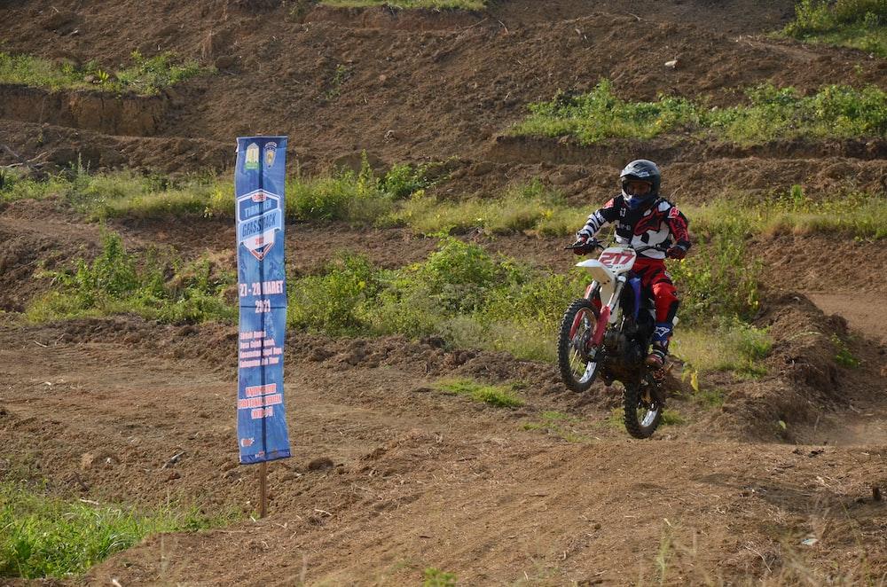 man in red and black motocross helmet riding motocross dirt bike